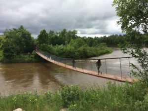 Walkers cross a rope bridge over the Roseau River in Manitoba