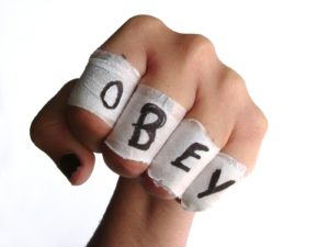 A white-skinned hand, making a fist, with the word OBEY written on tape wrapped around each finger