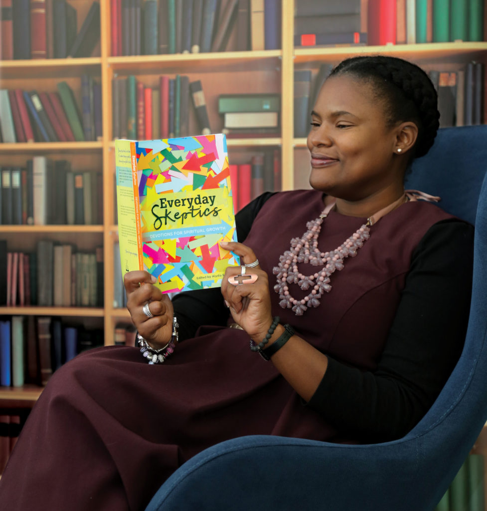 Alydia Smith, the editor of 'Everyday Skeptics', sits in a chair looking at the text of the book, holding it so that the cover is clearly visible. It features multicoloured arrows going in many directions.